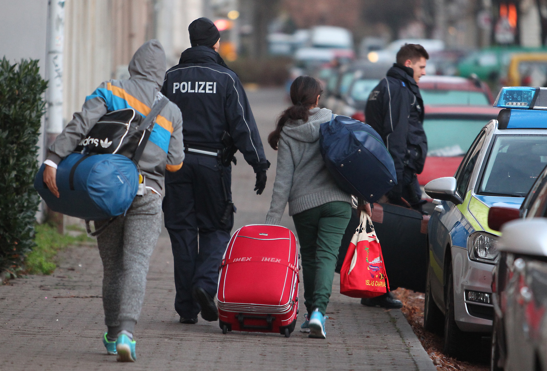German police bringing refugees back to the airport