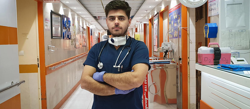 Young refugee Moheyman Alkhatavi can be seen in the hallway of a hospital where he works as a nurse treating COVID-19 patients. He wears the official workwear of a nurse, and has a face mask and stethoscope hanging around his neck.