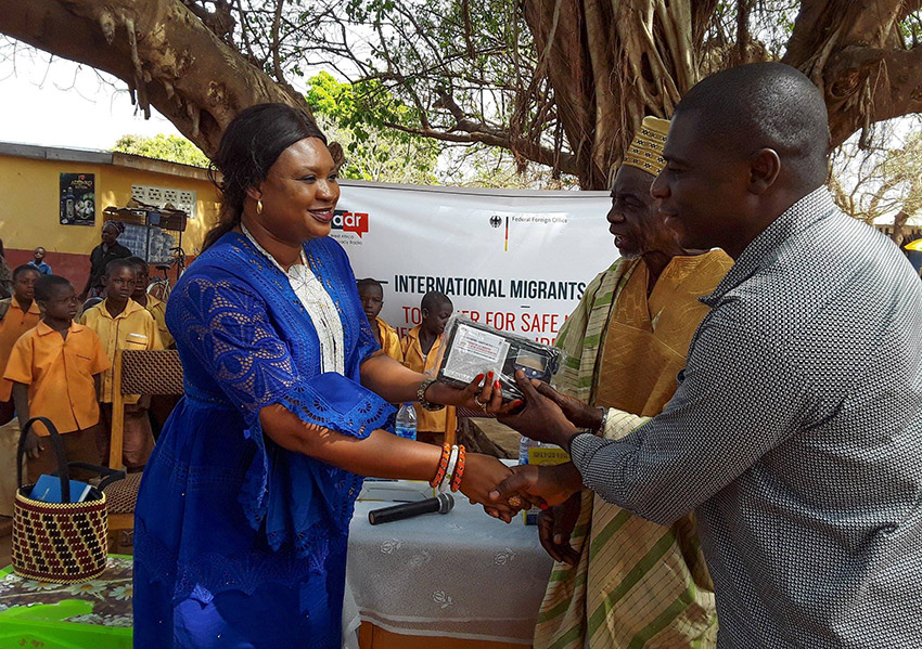 WADR station manager Agnes Thomasi is standing on the left, greeting two community members in Ghana at a ceremony on International Migrants Day. As a gift, Agnes Thomasi hands over radio equipment.