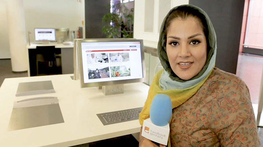 Reporter Sharmila Hashimi from Handbookgermany.de sitting in her office holding a microphone in front of her desktop computer in preparation for a show.