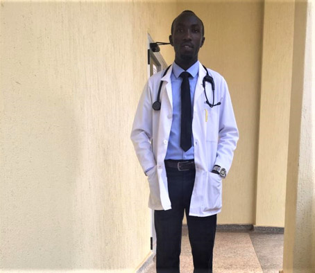 """Dr Jonas"", a young Congolese doctor, is standing in the middle of an empty hallway of a hospital, wearing the white workwear of a medical practitioner, with a stethoscope hanging loosely around his neck."